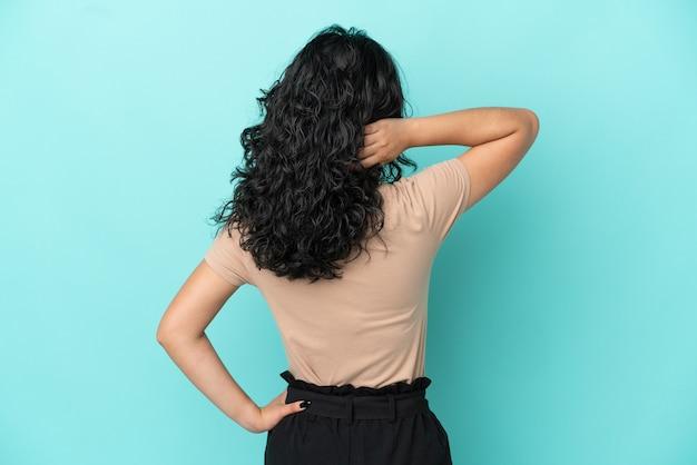 Молодая азиатская женщина изолирована на синем фоне в задней позиции и мышлении