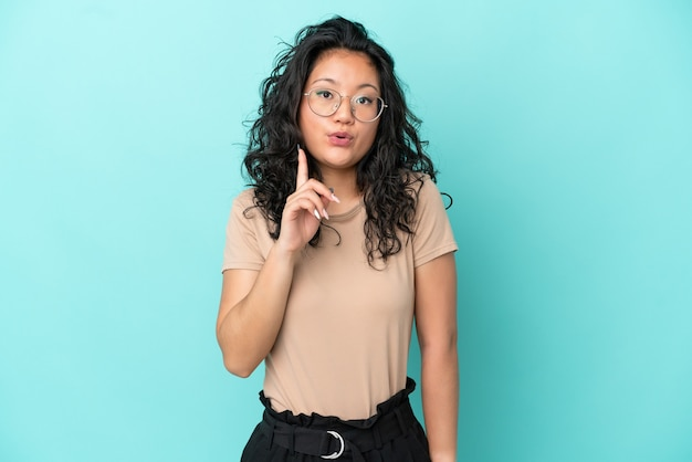 Молодая азиатская женщина изолирована на синем фоне, намереваясь реализовать решение, подняв палец вверх