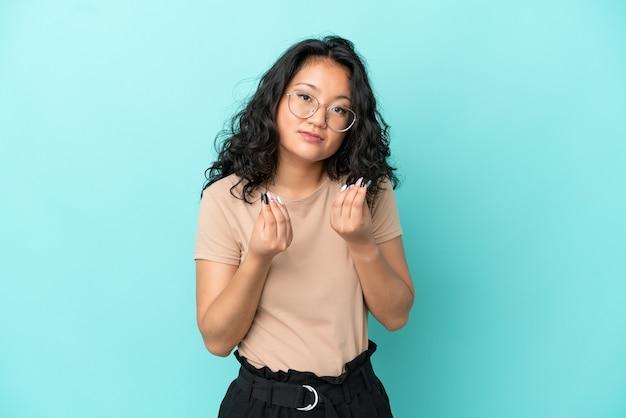 お金のジェスチャーを作る青い背景で隔離の若いアジアの女性が台無しになっている