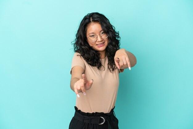 Молодая азиатская женщина изолирована на синем фоне указывая фронт с счастливым выражением лица