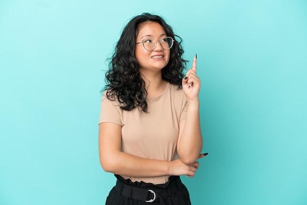 素晴らしいアイデアを指している青い背景に分離された若いアジアの女性