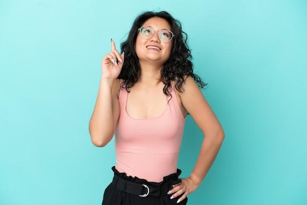 Молодая азиатская женщина изолирована на синем фоне указывая вверх и удивлена