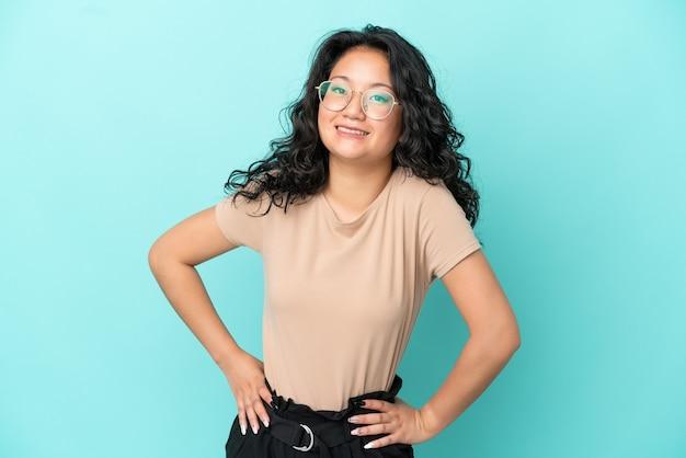 腰に腕と笑顔でポーズをとって青い背景で隔離の若いアジアの女性