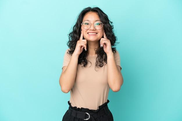 Молодая азиатская женщина изолирована на синем фоне, улыбаясь счастливым и приятным выражением лица