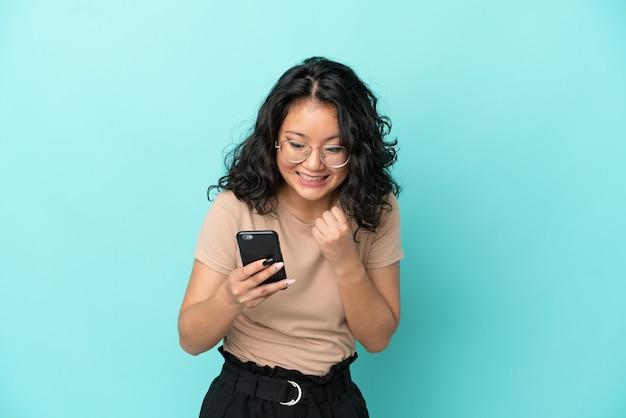 Молодая азиатская женщина, изолированная на синем фоне, удивлена и отправляет сообщение