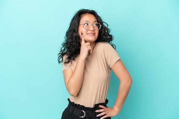 見上げながらアイデアを考えて青い背景で隔離の若いアジアの女性