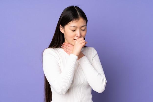 たくさん咳をする紫色の背景で隔離の若いアジアの女性