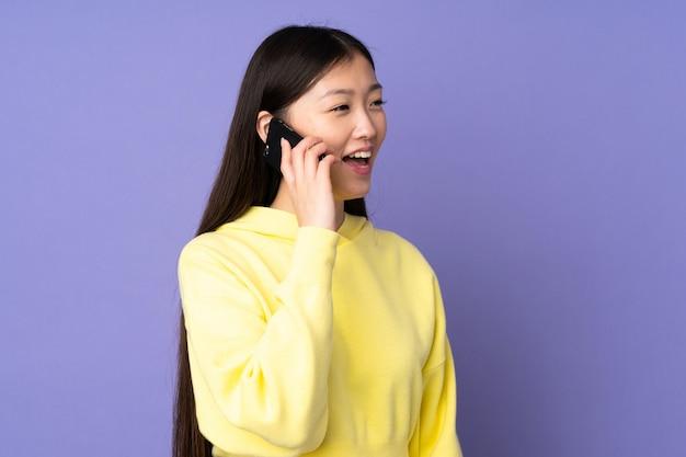 携帯電話との会話を維持する紫色の背景に分離された若いアジアの女性