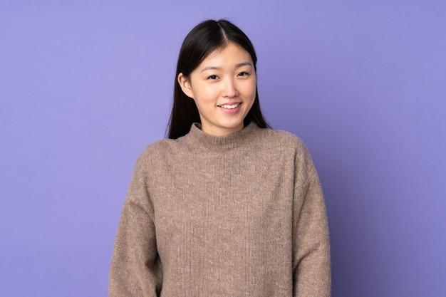 笑って紫色の背景に分離された若いアジアの女性