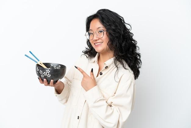 Молодая азиатская женщина изолирована на белом фоне и указывает на нее, держа миску лапши с палочками для еды