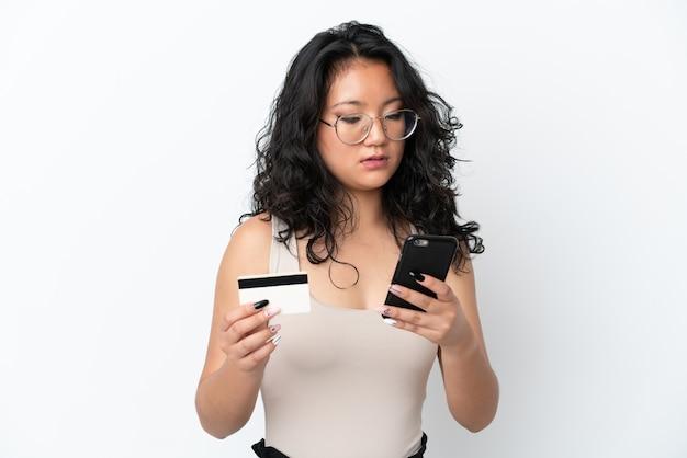 Молодая азиатская женщина, изолированная на белом фоне, покупая с мобильного телефона с помощью кредитной карты