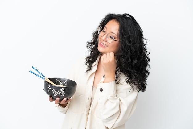 Молодая азиатская женщина изолирована на белом фоне празднует победу, держа миску лапши с палочками для еды