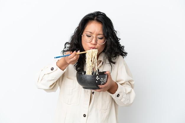 Молодая азиатская женщина, изолированная на белом фоне, держит миску лапши с песком для еды, дует, потому что они горячие