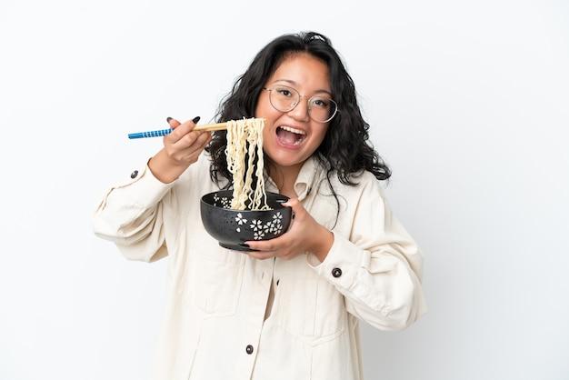 Молодая азиатская женщина, изолированная на белом фоне, держит миску лапши с палочками для еды и ест ее