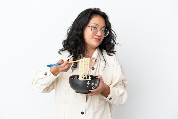 Молодая азиатская женщина изолирована на белом фоне, держа миску лапши с палочками для еды