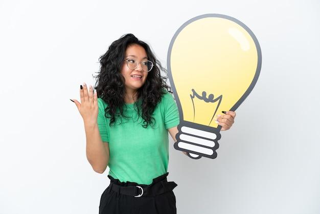Молодая азиатская женщина, изолированная на белом фоне, держит значок лампочки с удивленным выражением лица