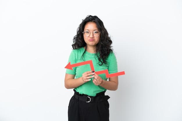 下向き矢印を保持し、悲しい表情で白い背景で隔離の若いアジアの女性