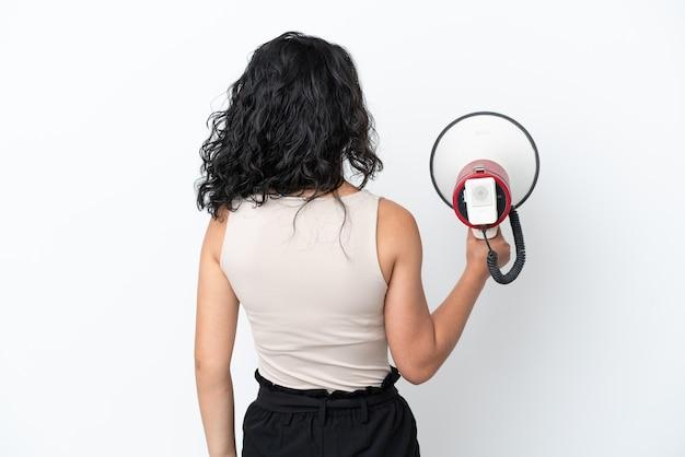Молодая азиатская женщина изолирована на белом фоне, держа мегафон и в задней позиции