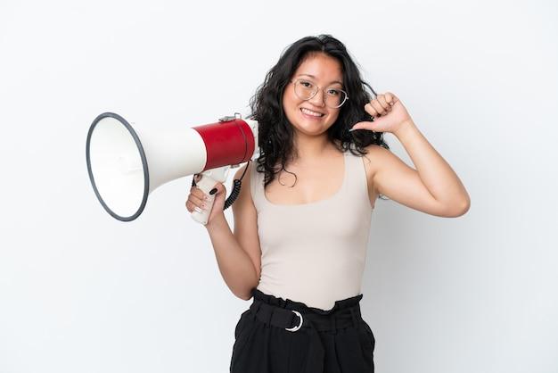 Молодая азиатская женщина, изолированная на белом фоне, держит мегафон и гордая и самодовольная