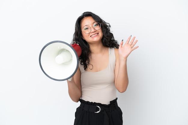Молодая азиатская женщина изолирована на белом фоне, держа мегафон и салютуя рукой с счастливым выражением лица