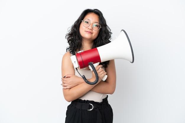 Молодая азиатская женщина, изолированная на белом фоне, держит мегафон и улыбается