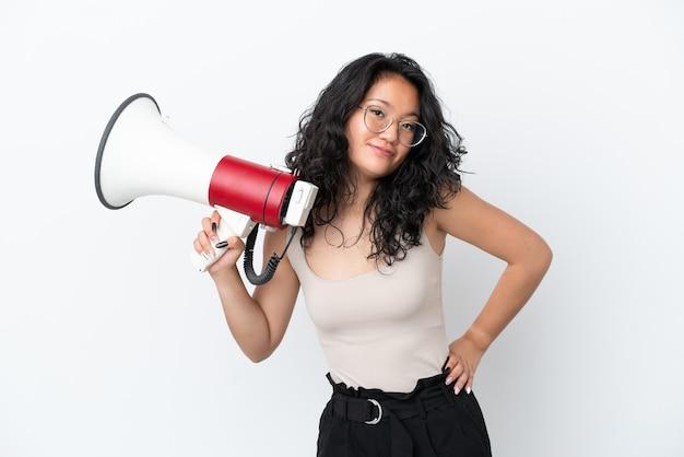 Молодая азиатская женщина изолирована на белом фоне, держа мегафон и думая