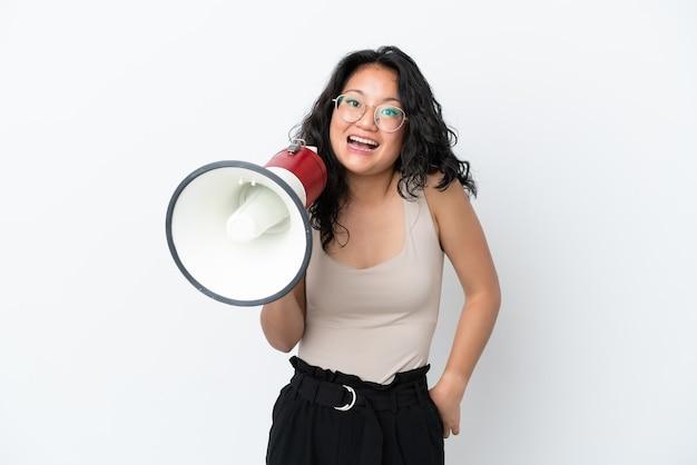 メガホンを保持し、驚きの表情で白い背景で隔離の若いアジアの女性