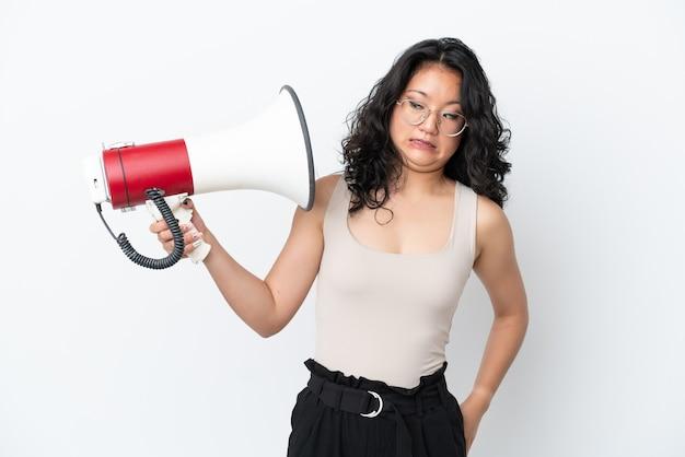 Молодая азиатская женщина, изолированная на белом фоне, держит мегафон с подчеркнутым выражением лица