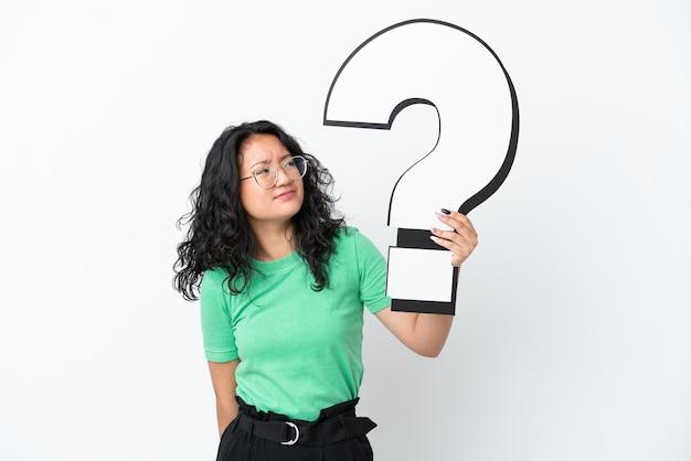 Молодая азиатская женщина, изолированная на белом фоне, держит значок вопросительного знака и сомневается