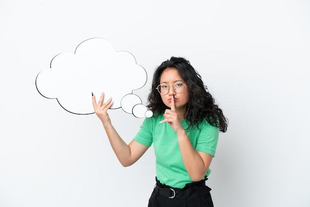 Молодая азиатская женщина изолирована на белом фоне, держа мысленный речевой пузырь и делая жест молчания