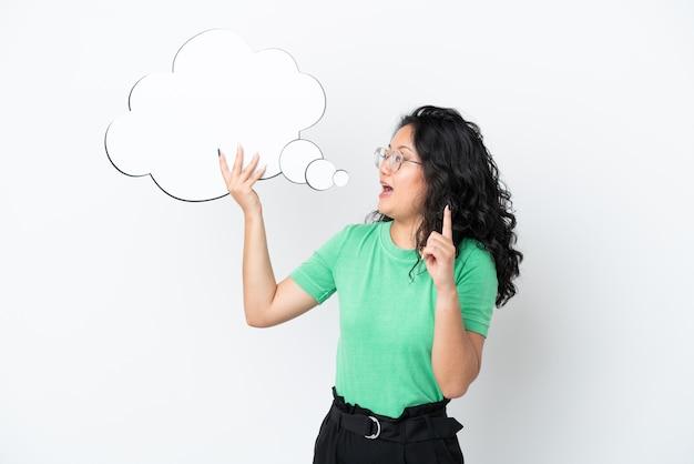 Молодая азиатская женщина изолирована на белом фоне, держа мыслящий речевой пузырь с удивленным выражением лица