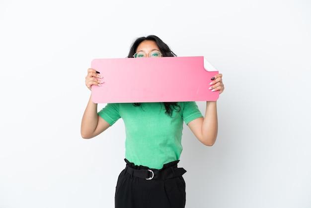 空のプラカードを保持し、その後ろに隠れて白い背景で隔離の若いアジアの女性