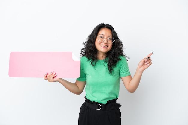 Молодая азиатская женщина изолирована на белом фоне, держа пустой плакат и указывая сторону