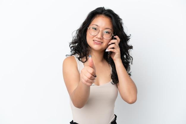 Молодая азиатская женщина изолирована на белом фоне, поддерживая разговор с мобильным телефоном, делая большие пальцы руки вверх