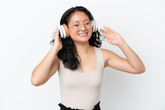 音楽を聴いて歌う白い背景で隔離の若いアジアの女性