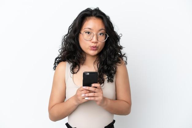 Молодая азиатская женщина изолирована на белом фоне, глядя в камеру, используя мобильный телефон с удивленным выражением лица