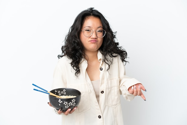 흰색 배경에 격리된 젊은 아시아 여성이 젓가락으로 국수 한 그릇을 들고 어깨를 들어올리면서 의심하는 제스처를 취합니다.
