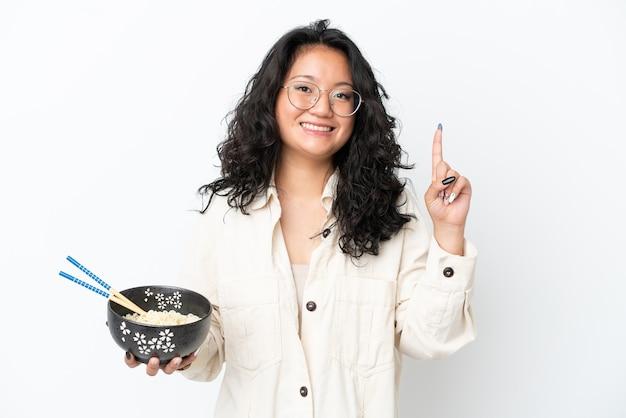 箸で麺のボウルを保持しながら素晴らしいアイデアを指している白い背景で隔離の若いアジアの女性