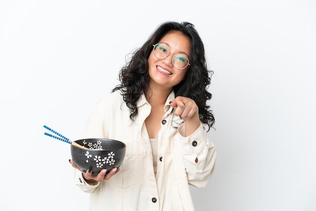 白い背景で隔離の若いアジアの女性は、箸で麺のボウルを保持しながら自信を持ってあなたに指を指しています