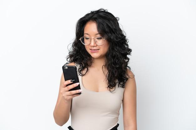 흰색 배경에 격리된 젊은 아시아 여성이 모바일로 메시지나 이메일을 보냅니다.