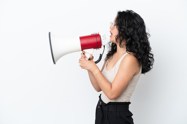 흰색 배경에 격리된 젊은 아시아 여성이 확성기를 통해 측면 위치에서 무언가를 발표하도록 외쳤다