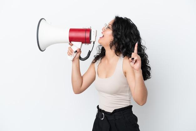 Молодая азиатская женщина, изолированная на белом фоне, кричит в мегафон, чтобы объявить что-то в боковом положении