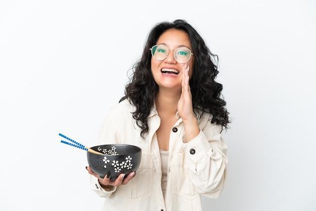 Молодая азиатская женщина изолирована на белом фоне кричит с широко открытым ртом, держа миску лапши с палочками для еды
