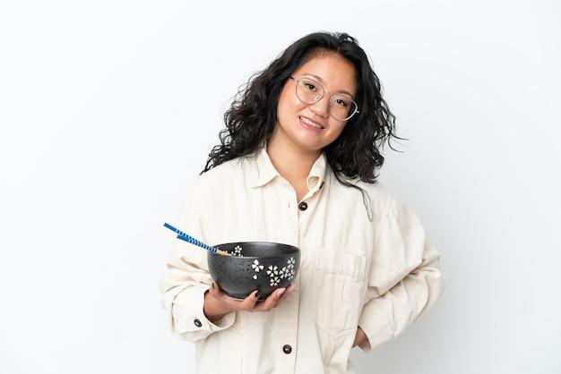 Молодая азиатская женщина изолирована на белом фоне, много улыбаясь, держа миску лапши с палочками для еды