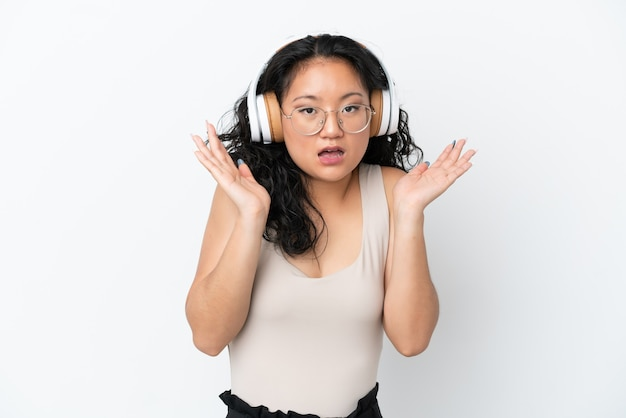 Молодая азиатская женщина изолирована на белом фоне удивлена и слушает музыку