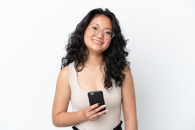 Молодая азиатская женщина изолирована на белом фоне с помощью мобильного телефона