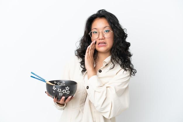 箸で麺のボウルを保持しながら何かをささやく白い背景で隔離の若いアジアの女性