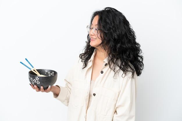 Молодая азиатская женщина изолирована на белом фоне со счастливым выражением лица, держа миску лапши с палочками для еды
