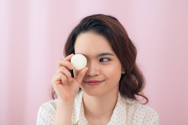 Young asian woman over isolated pink wall holding colorful macarons and eating it
