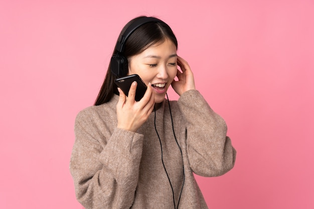 Young asian woman isolated on pink wall listening music with a mobile and singing